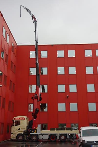 Lutter Spedition NRW - Betriebsumzüge - Maschinentransport - Logistik - Lkw mit Kran ausgefahren über ein 5-stoeckiges Haus