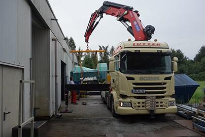Lutter Spedition NRW - Betriebsumzüge - Maschinentransport - Logistik - Lkw mit Kran hebt eine Maschine auf die Ladeflaeche